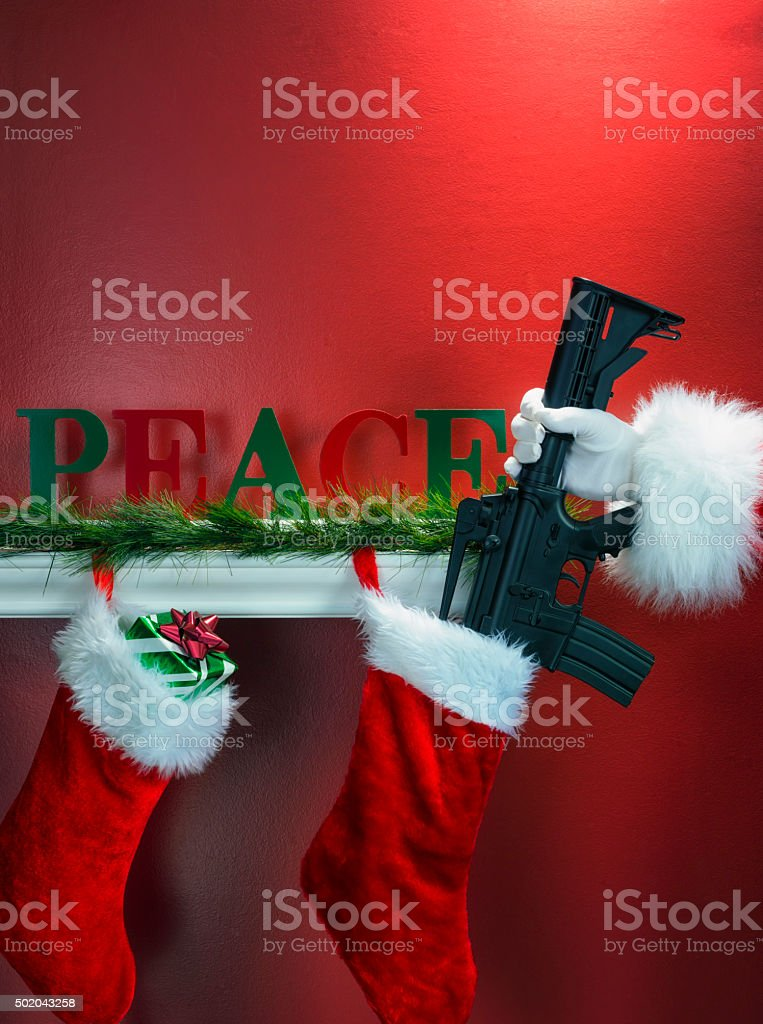 Santa stuffing an assault weapon into a Christmas Stockings stock photo