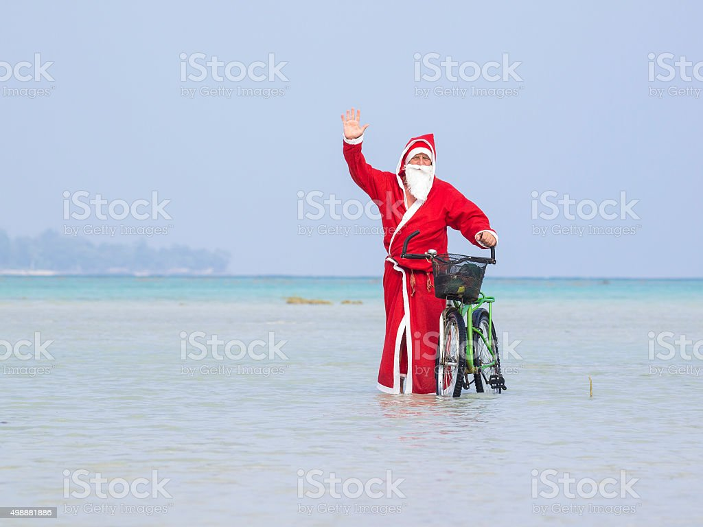 Santa with bike coming out of sea on Andamans stock photo