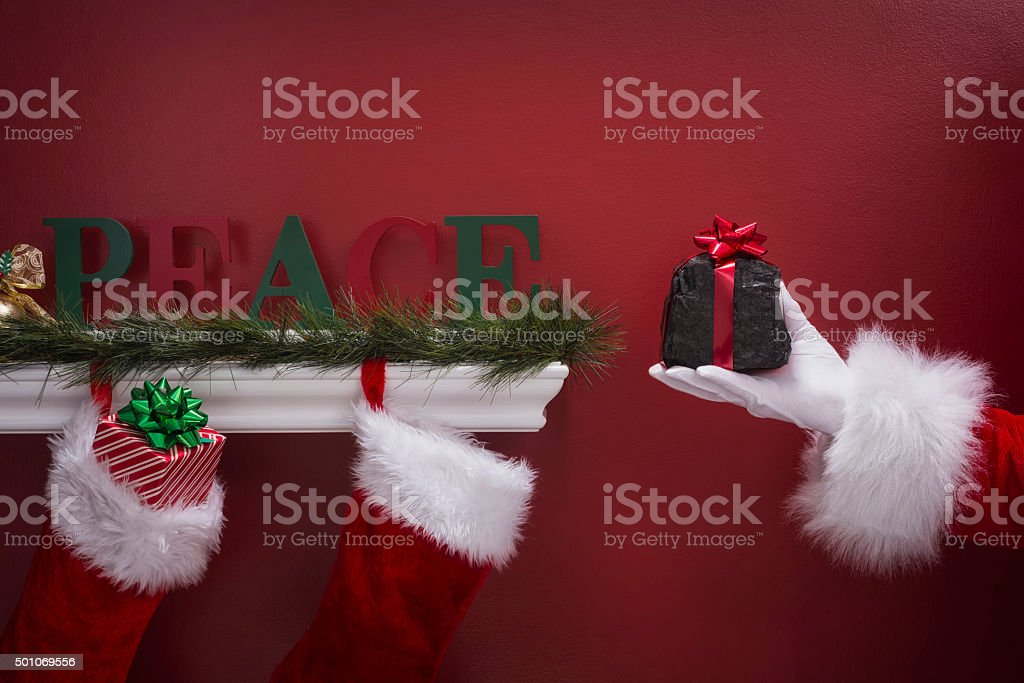 Santa's hand holding coal next to Christmas Stockings stock photo