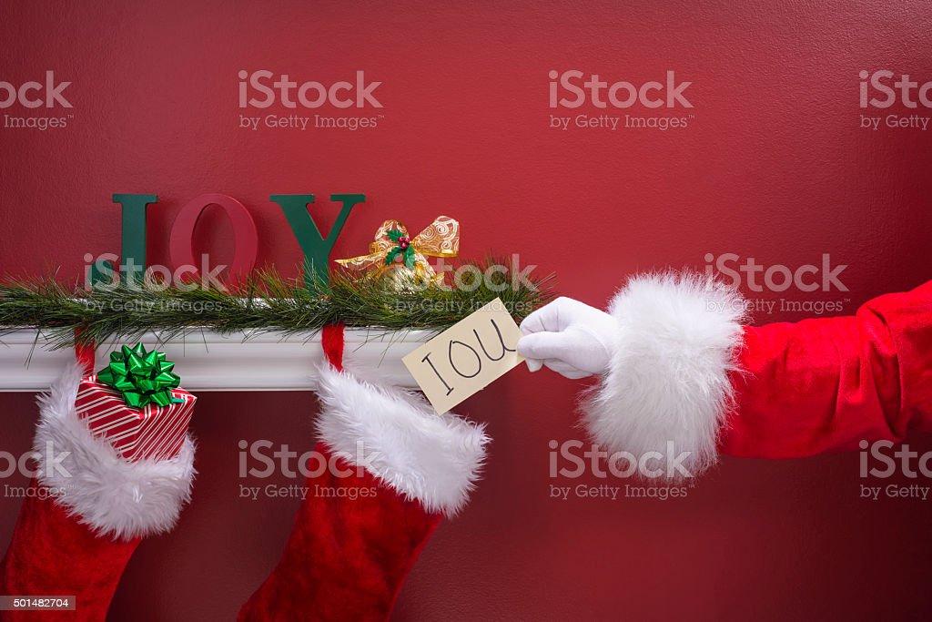 Santa's hand placing an IOU note into Christmas Stockings stock photo