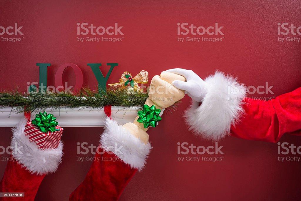 Santa's hand placing large rawhide dog bone into Christmas Stockings stock photo