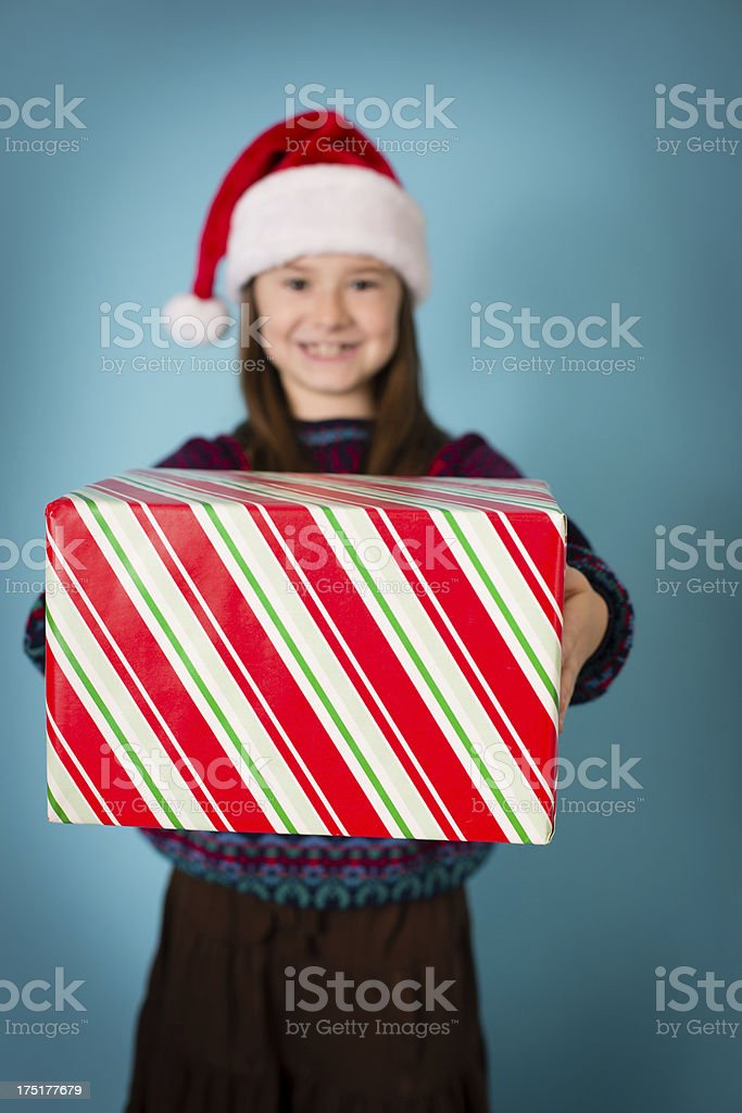Santa's Happy Little Helper Wearing Hat and Holding Christmas Gift royalty-free stock photo