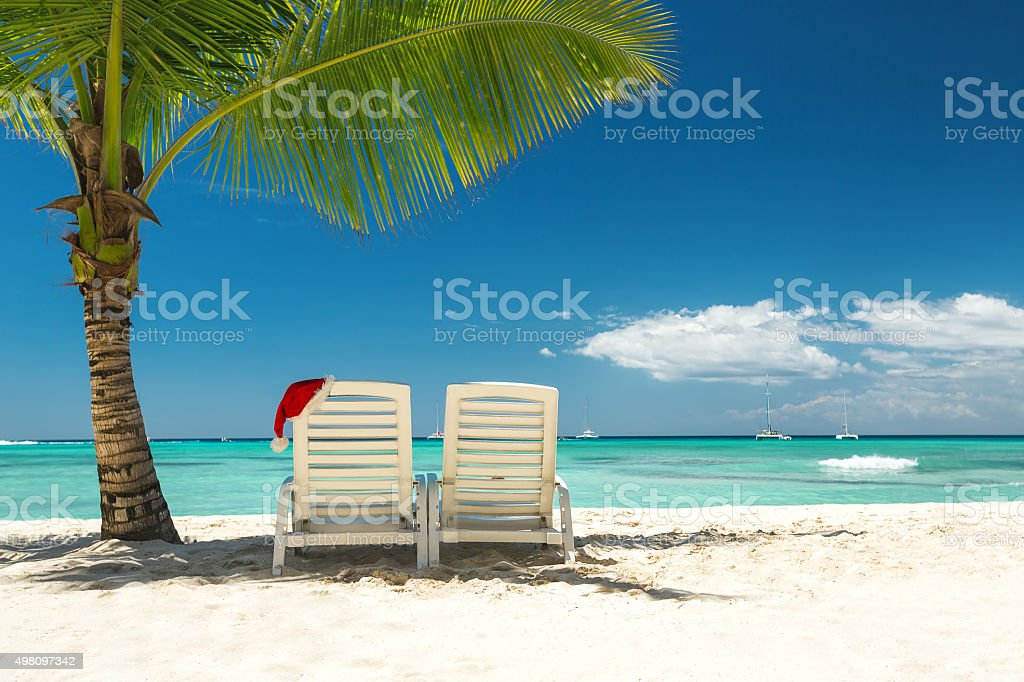 Santa's hat and sun loungers on the tropical beach stock photo