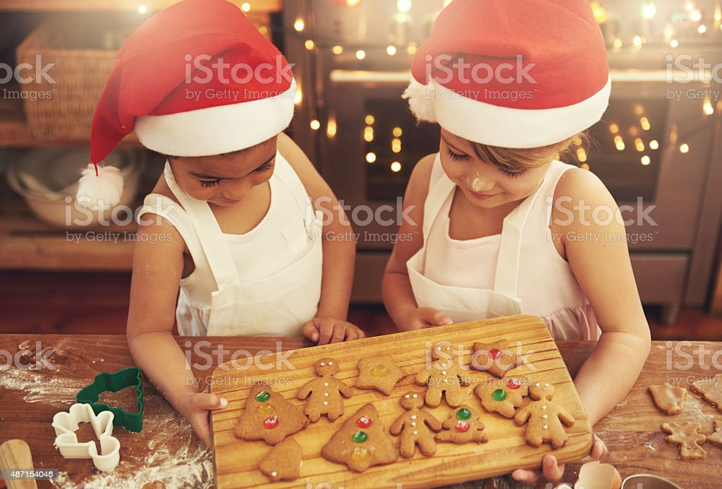 Shot of two little girls baking Christmas cookies in the...
