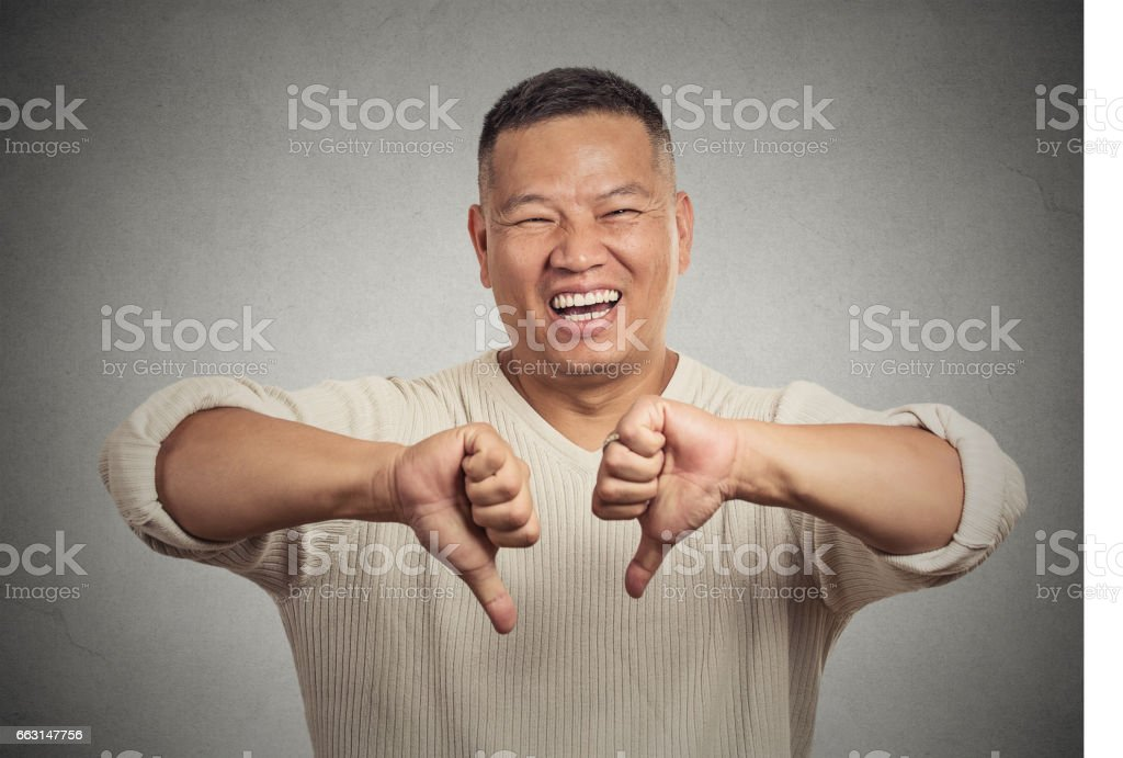 sarcastic young man showing two thumbs down sign hand gesture stock photo