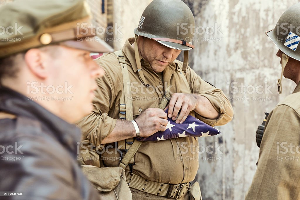 Sargeant Folding the American Flag after the Loss of Comrade stock photo