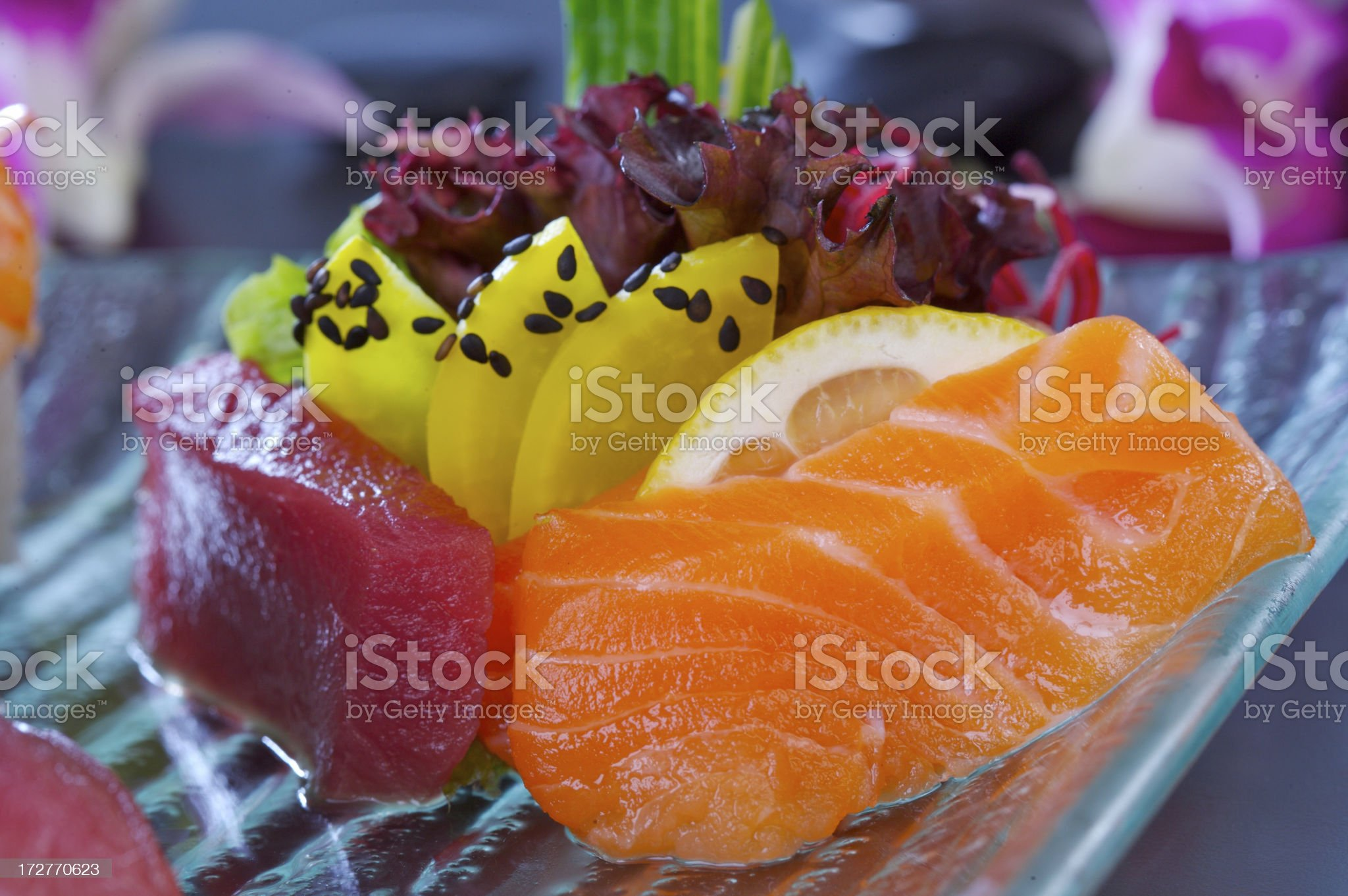 Sashimi arranged with fruit on a square glass dish royalty-free stock photo