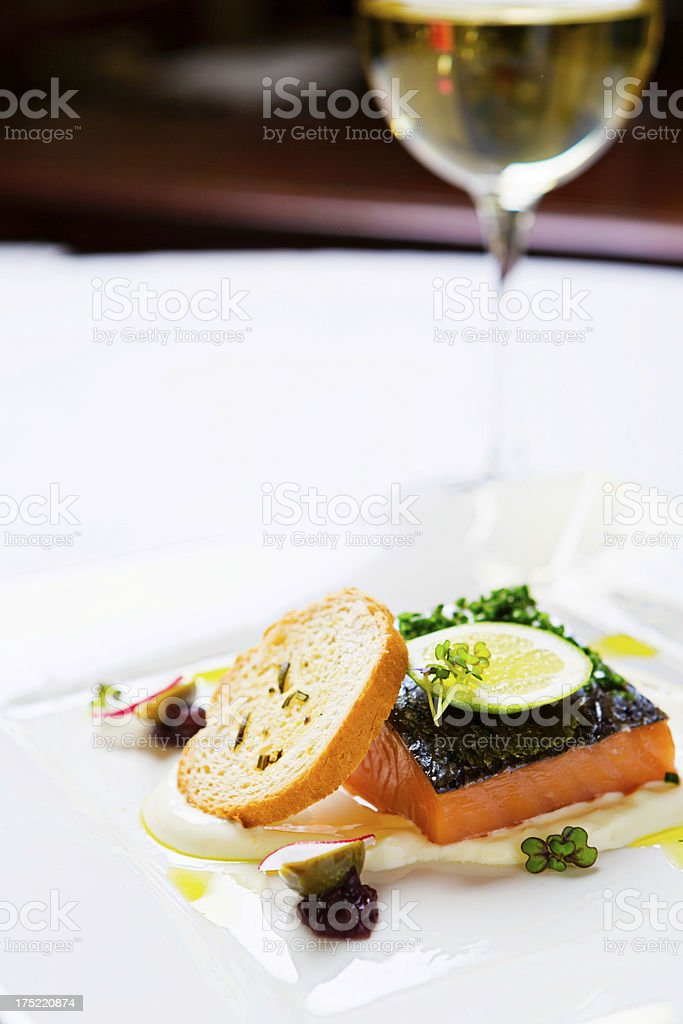 Sashimi-grade salmon dish with glass of white wine in restaurant stock photo