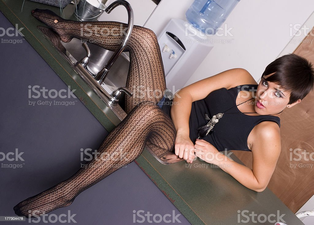 Sassy Young Woman in Lace Stockings on The Kitchen Sink stock photo