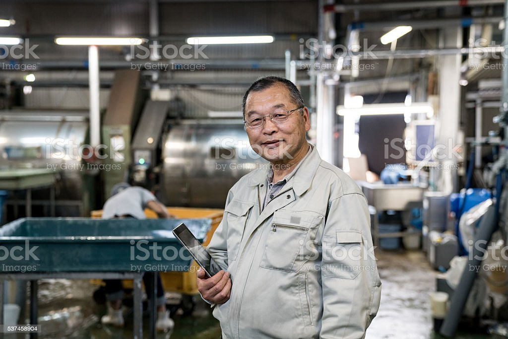 Sastisfied senior manager standing in a garment washing facility stock photo