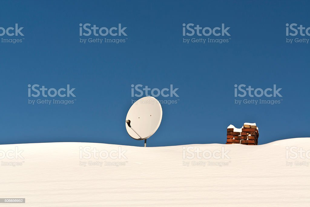 Satellite antenna and chimney on snowy roof. stock photo