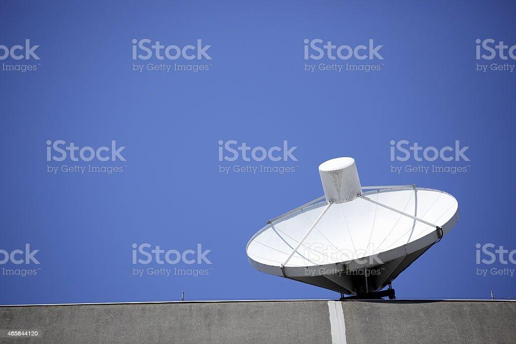 satellite dish and blue sky on concrete stock photo