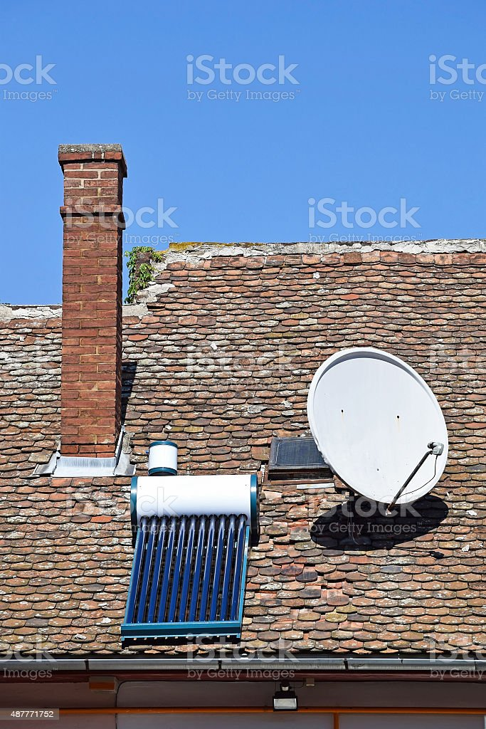 Satellite dish and solar heater on the roof stock photo