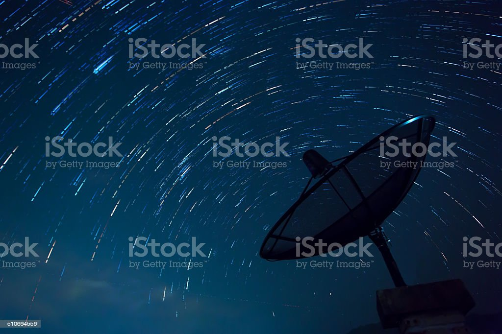 Satellite Dish and Star Trails. Blue sky. stock photo