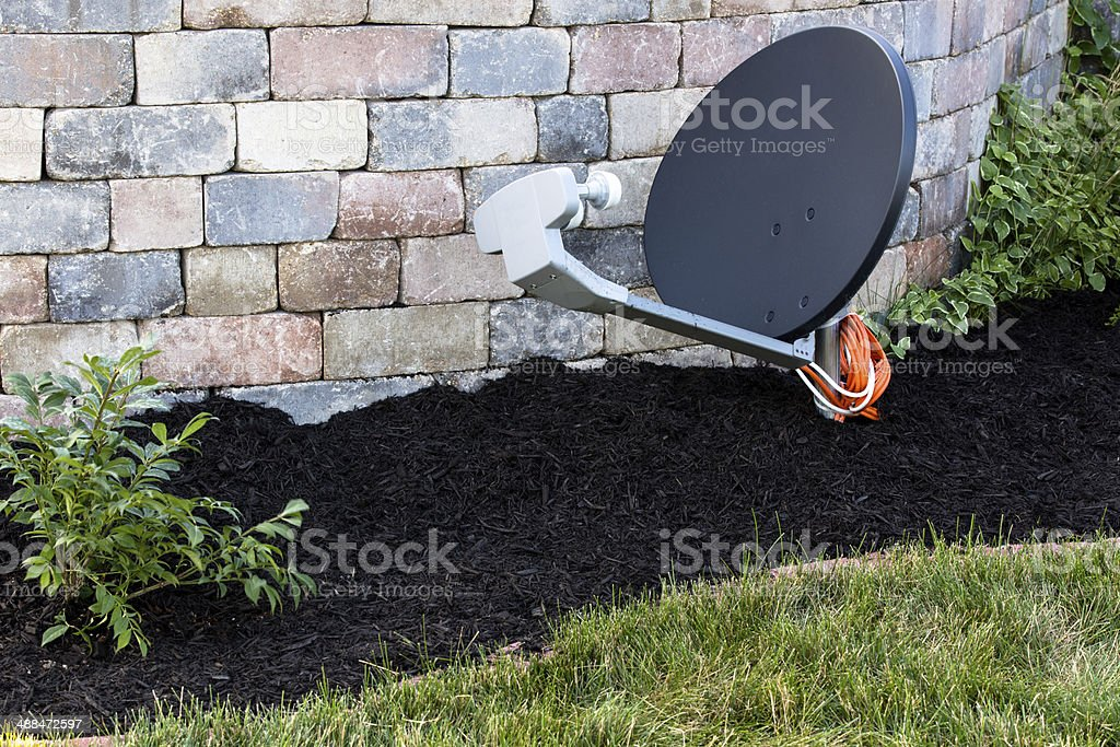 Satellite Dish Ground Mount by the Brick wall royalty-free stock photo