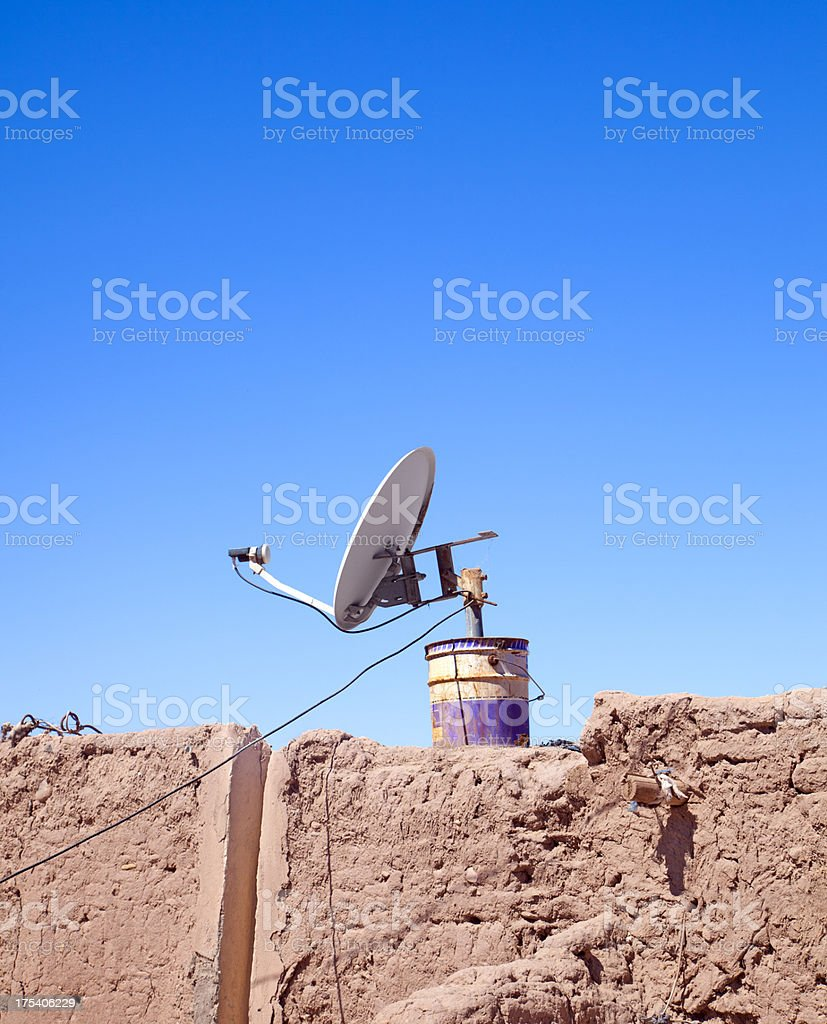 Satellite Dish in Bucket on Mud Wall stock photo