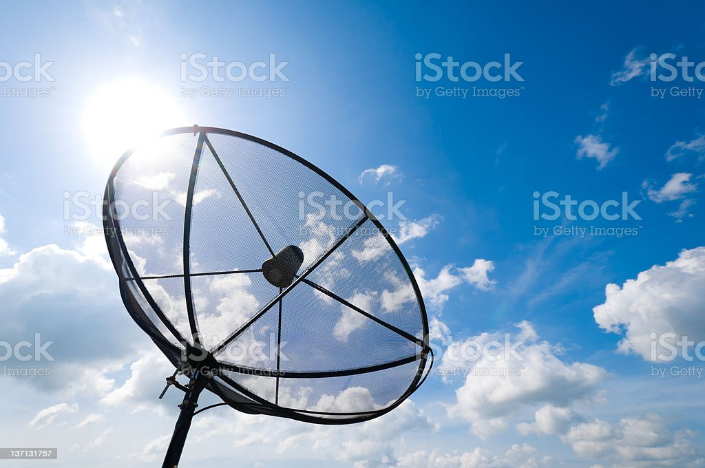 A satellite dish in front of a blue sky stock photo