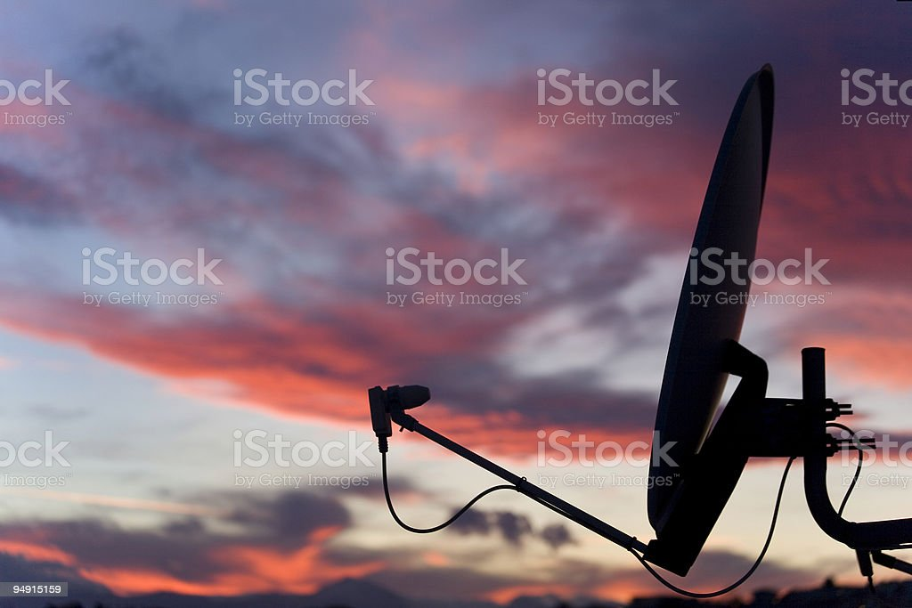 A satellite dish in front of a sunset sky  stock photo