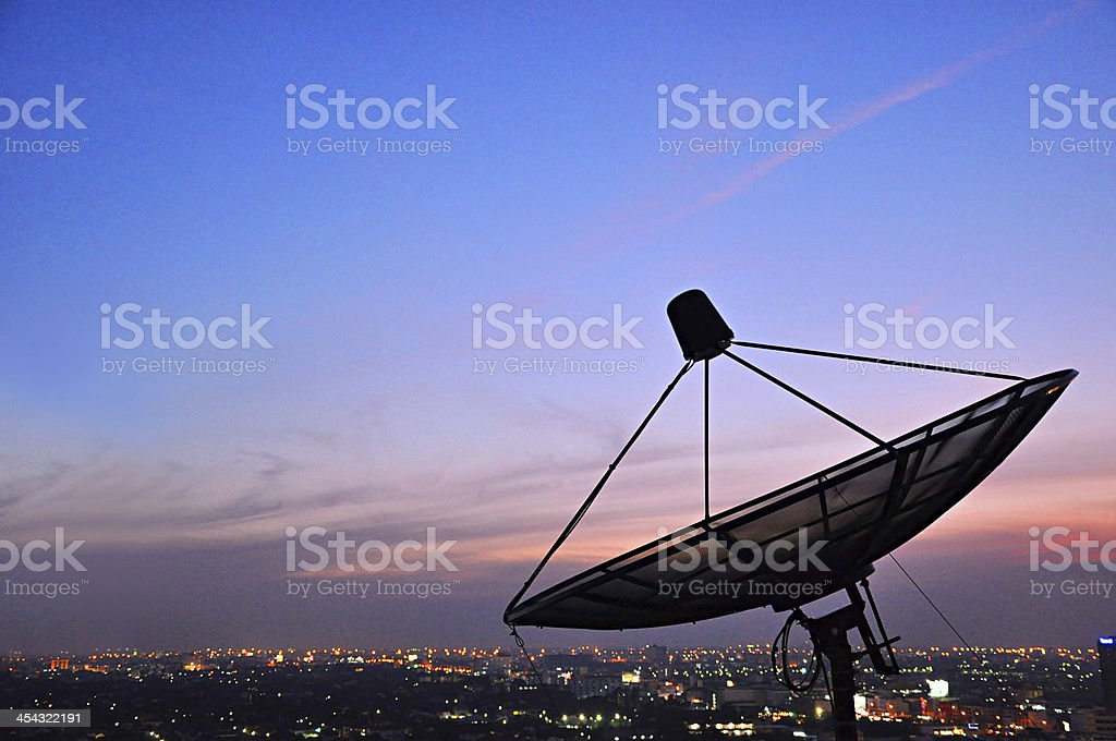 Satellite dish in twilight scene stock photo
