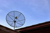 Satellite dish on the roof , blue sky background.