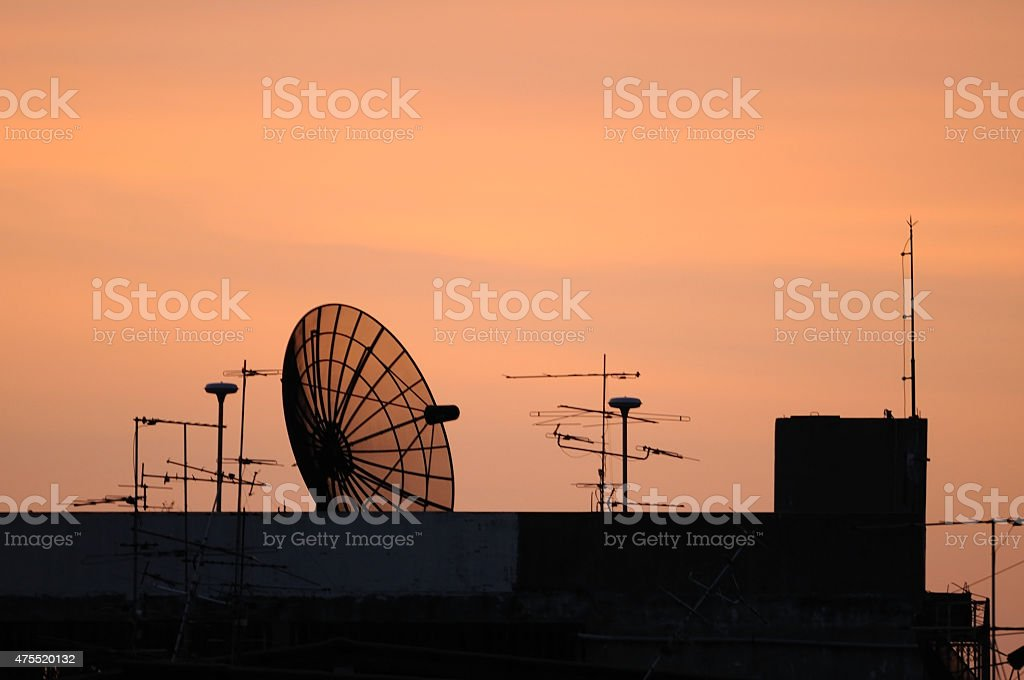 Satellite dish on top building during sunset time stock photo