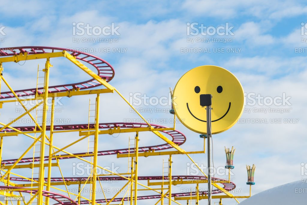 Satellite dish painted as a smilie with joyride in the backgound at a folk festival stock photo