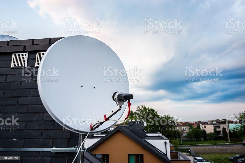 Satellite dish, satellite antenna mounted on the chimney stock photo