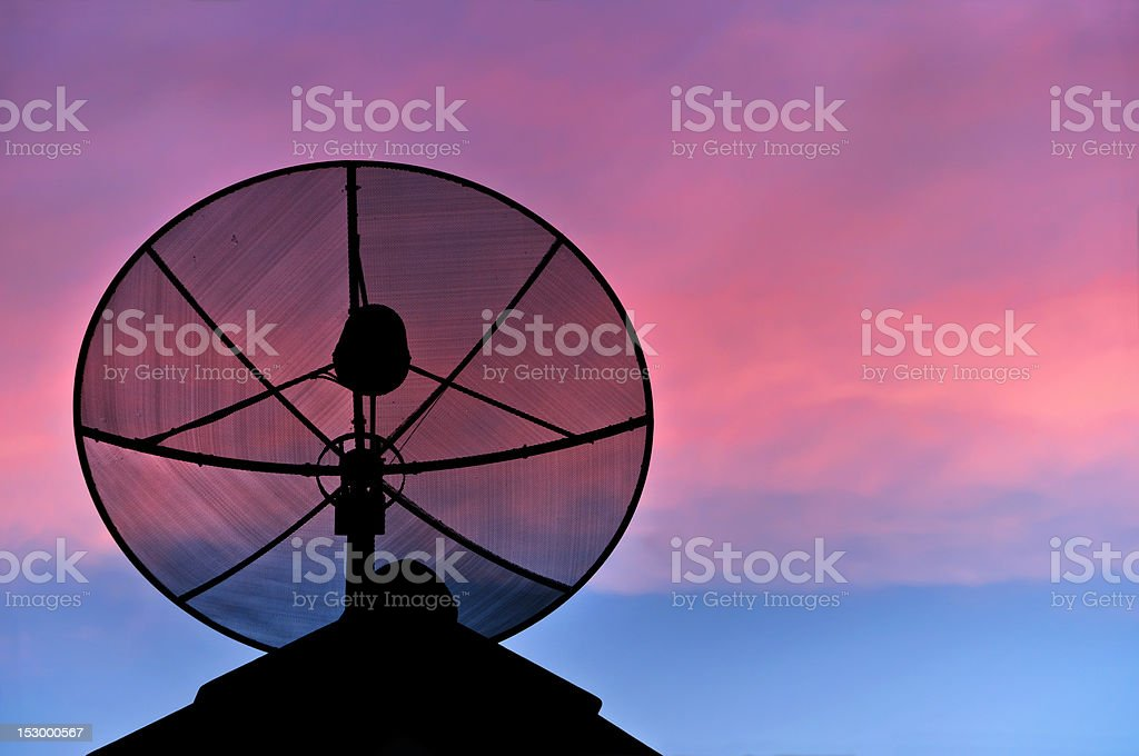 Satellite dish silhouette on the roof in evening sky. royalty-free stock photo