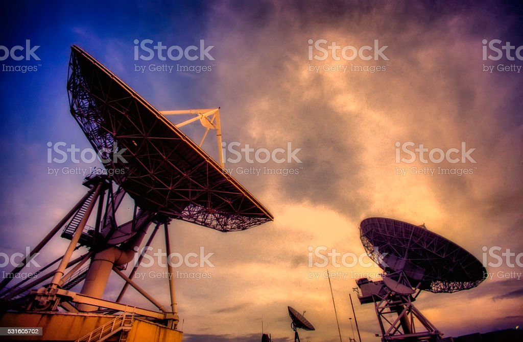 Satellite dishes at sunset stock photo