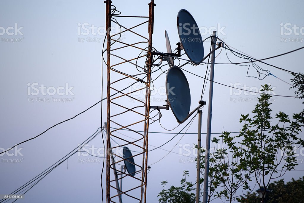 Satellite dishes on a metal pole by the tree top stock photo