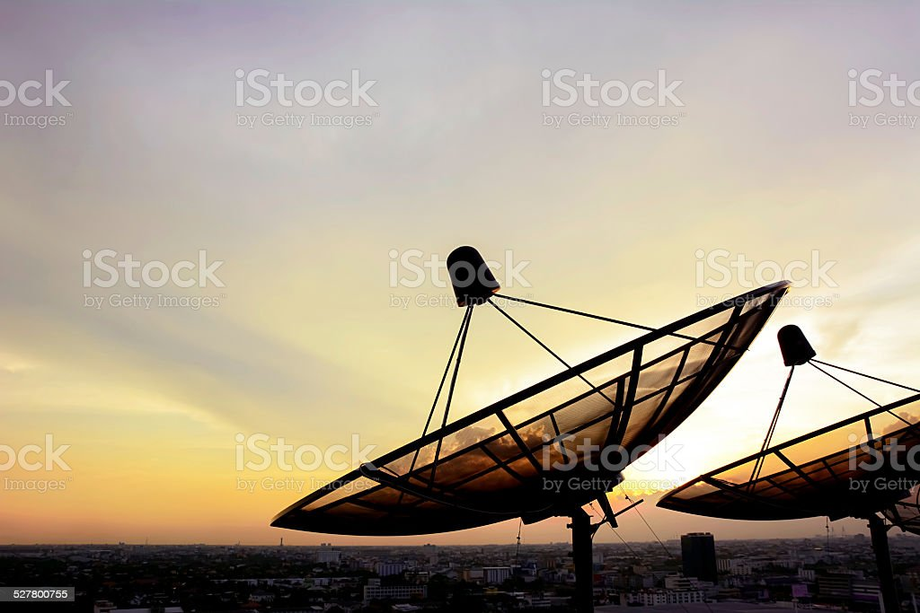 Satellite dishes on twilight sky background stock photo