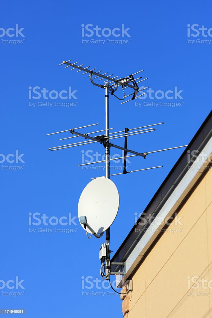 Satellite receiver dishes and TV antenna on blue sky royalty-free stock photo