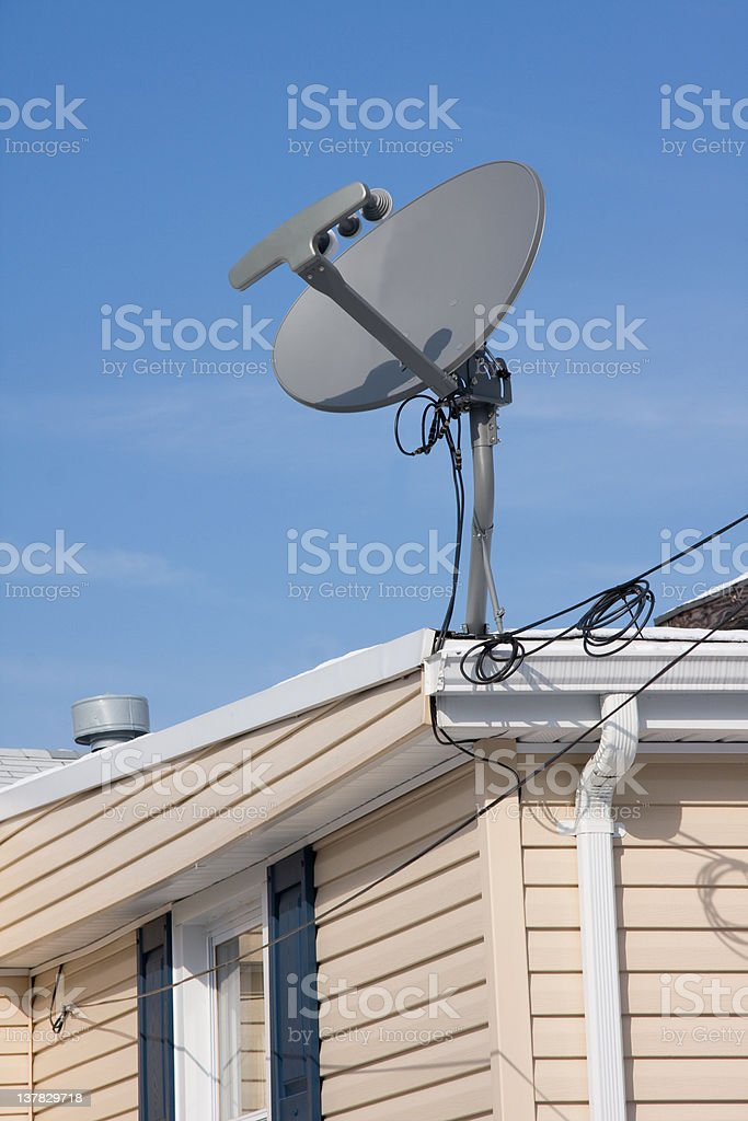 satellite TV antenna on the roof of a house royalty-free stock photo