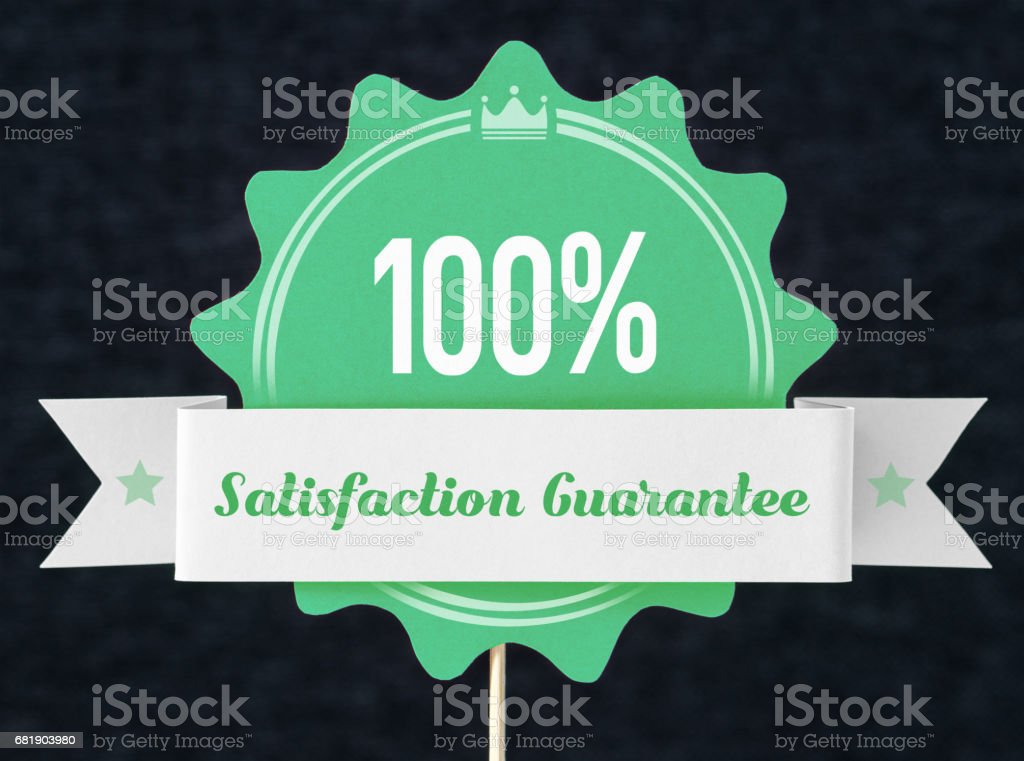 100% satisfaction guarantee badge cut from cardboard and paper on a wooden stick. Green banner, seal and ribbon for business website to promise customer the best premium quality product or service. stock photo
