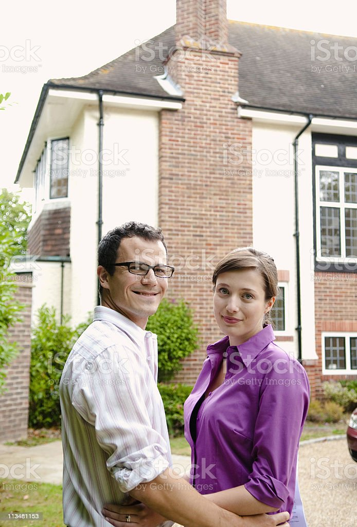 Satisfied couple outside new home stock photo