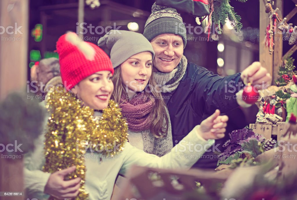 satisfied family couple with teen daughter choosing Christmas decoration stock photo