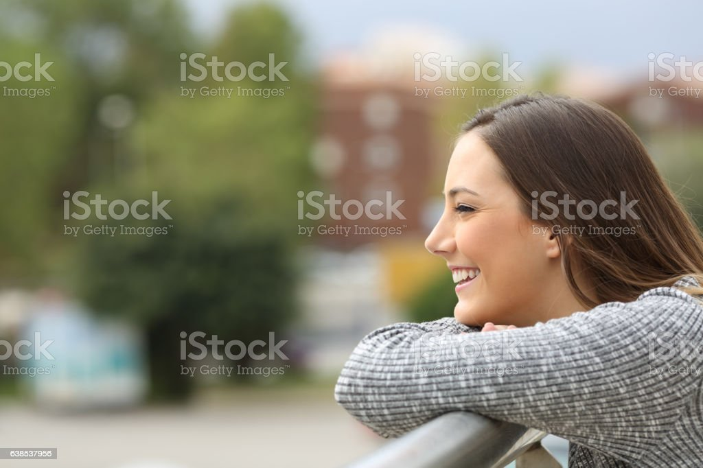 Satisfied girl looking away from a balcony stock photo