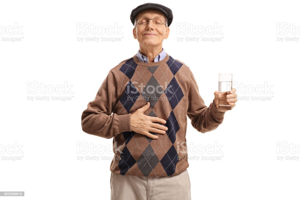 Satisfied senior with glass of water holding his hand on stomach stock photo