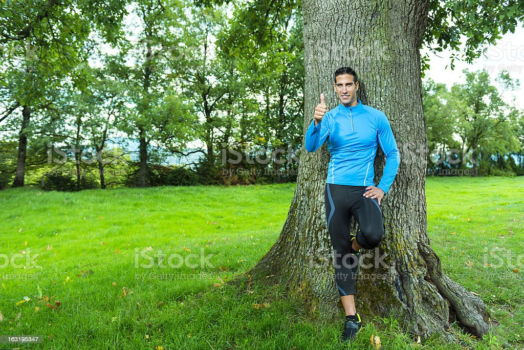 satisfied sportsman resting by tree royalty-free stock photo