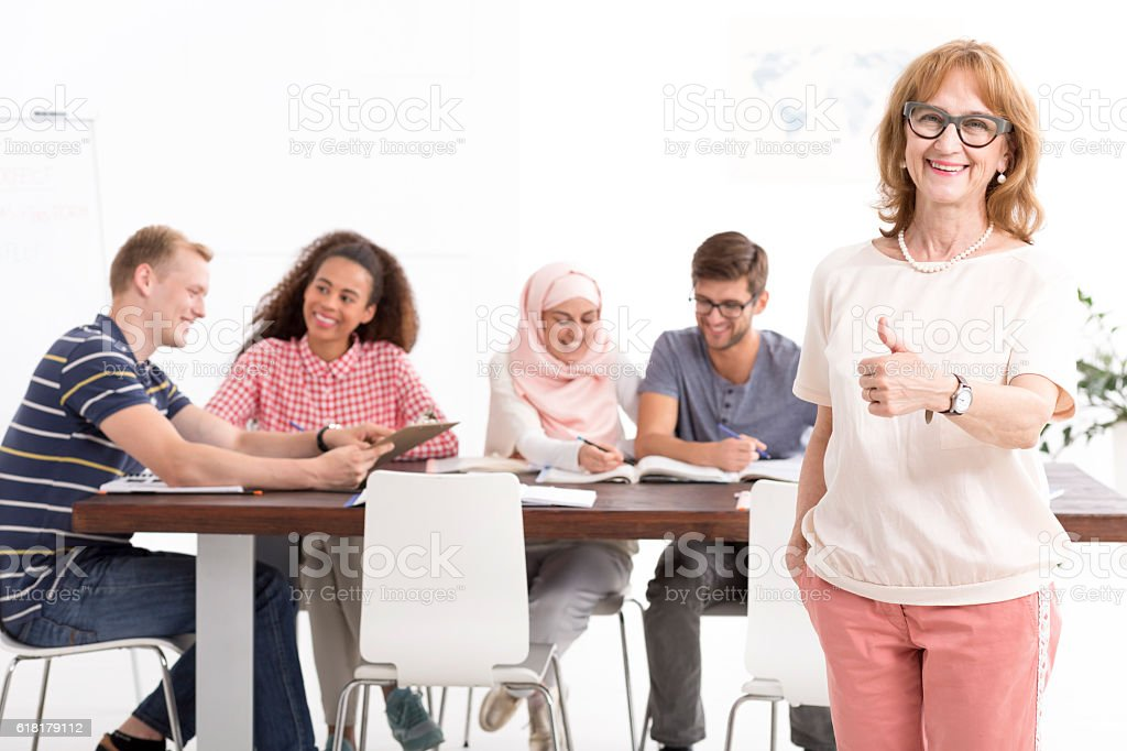 Satisfied teacher standing with the thumb up stock photo