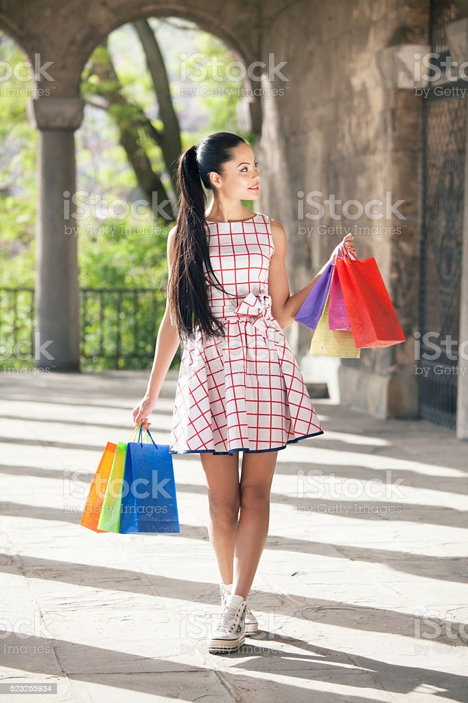Satisfied young woman holding colored purcheses stock photo
