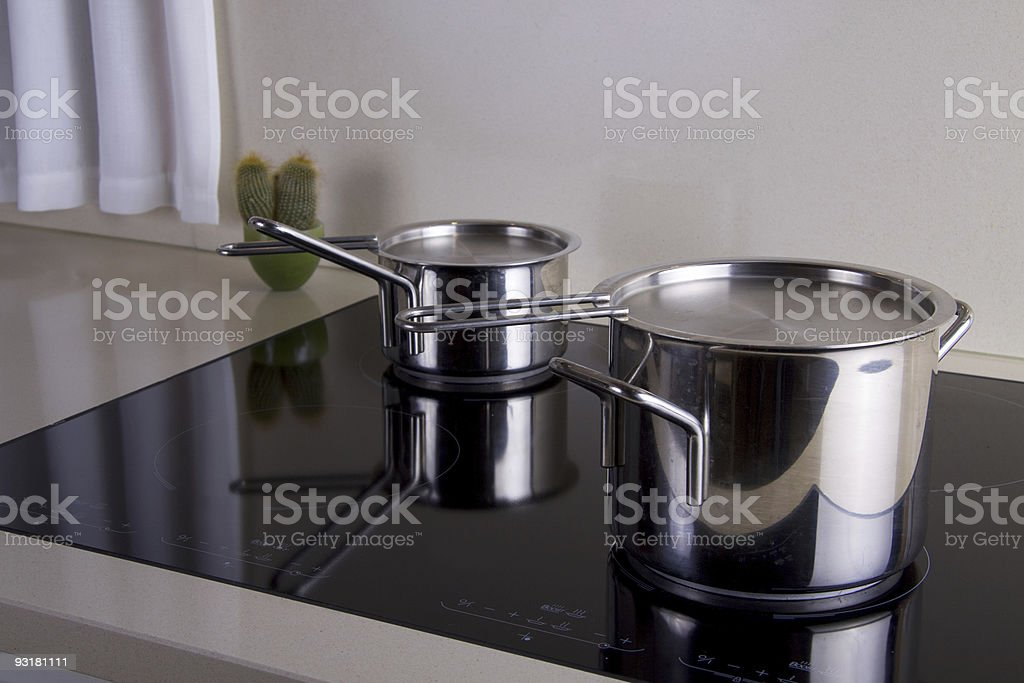 Sauce pans on hot plates stock photo