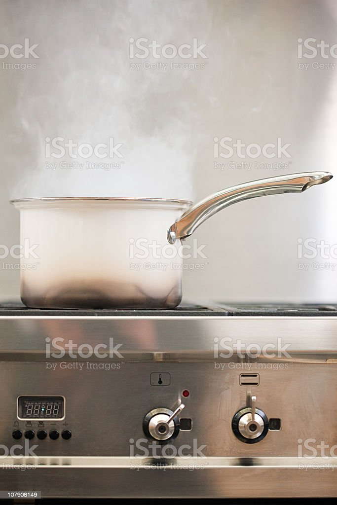 Saucepan boiling on hob with steam stock photo