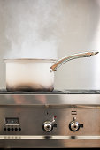 Saucepan boiling on hob with steam
