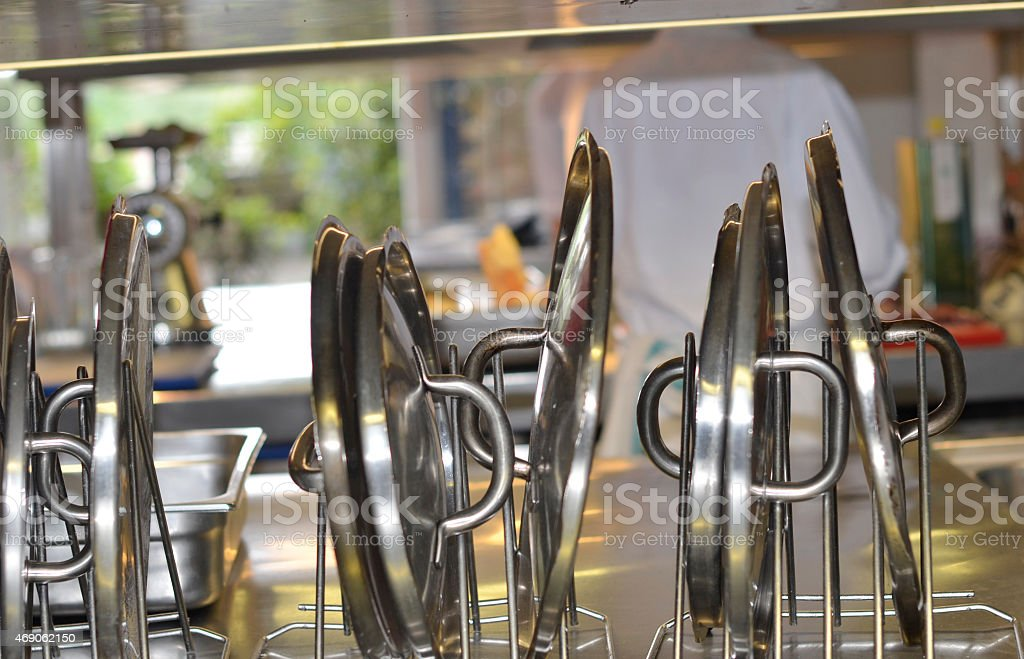 saucepan lids drying on a rack in a restaurant kitchen stock photo