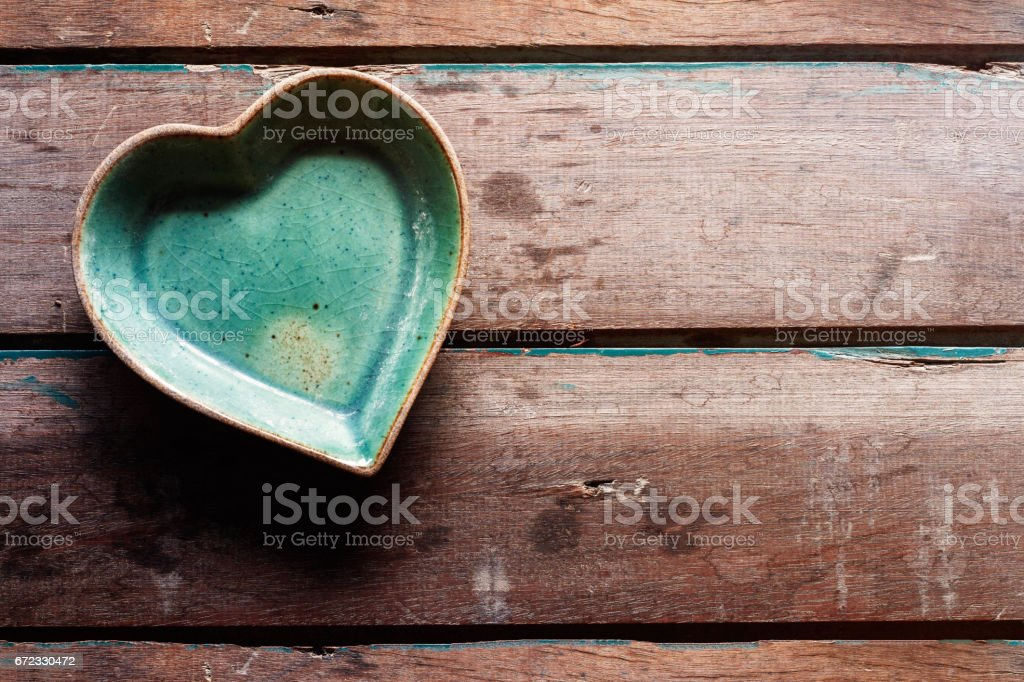 saucer of shaped heart on wood. stock photo