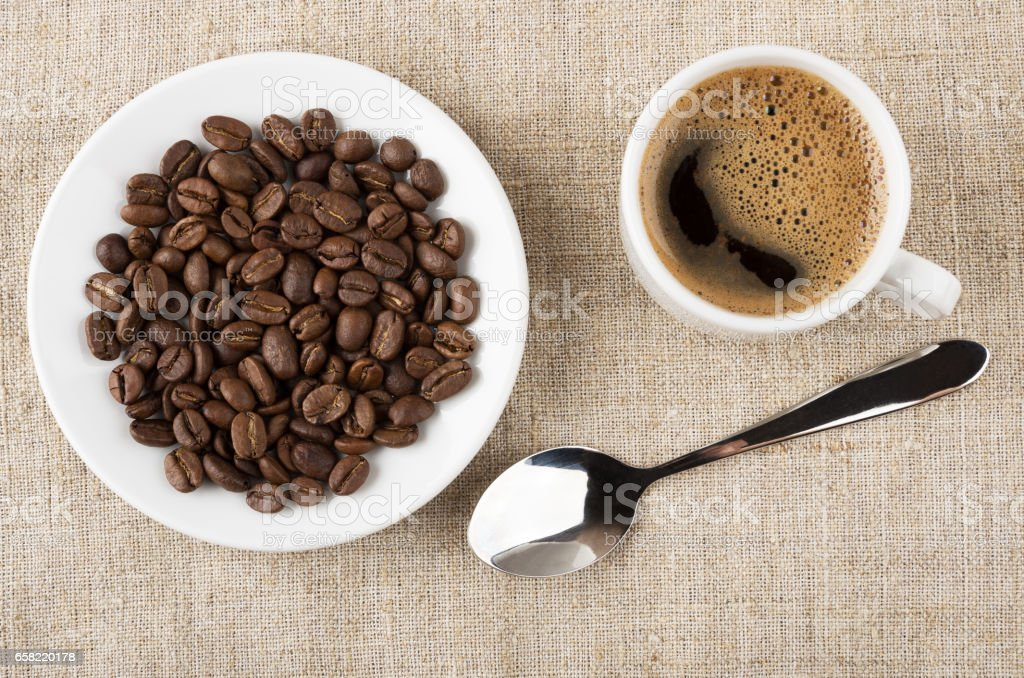 Saucer with coffee beans, cup of coffee and spoon stock photo