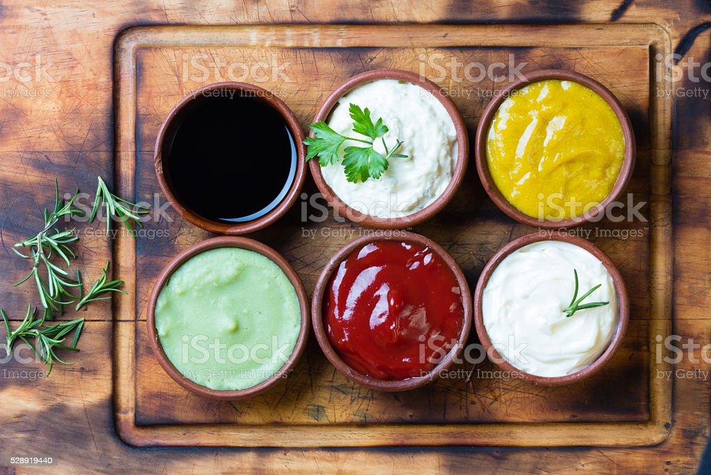 Sauces ketchup, mustar, mayonnaise, wasabi, soy sauce in clay bowls stock photo