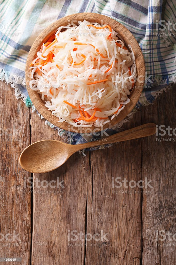 sauerkraut and carrots in a wooden plate. vertical top view stock photo