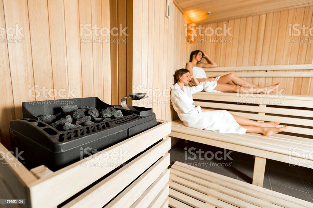 Sauna heater and girls relaxing stock photo